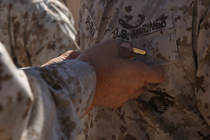 Maj. Gen. Daniel O'Donohue, the 1st Marine Division commanding general, pins a Marine with a super squad badge aboard Marine Corps Air-Ground Combat Center Twentynine Palms, Calif., Aug. 15, 2016. The Marines received the engraved badges for placing first in the 1st Marine Division Super Squad Competition that took place in July. (U.S. Marine Corps photo by Cpl. Timothy Valero)