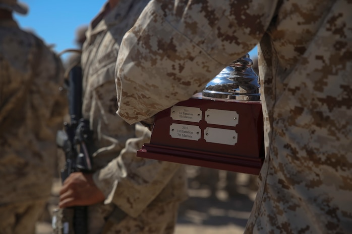 Sgt. Derrick Higgs, a squad leader with Company C, 1st Battalion, 7th Marine Regiment, holds the Mitchell Cup after a ceremony to recognize his squad's victory aboard Marine Corps Air-Ground Combat Center Twentynine Palms, Calif., Aug. 15, 2016. The Marines also received individually engraved badges for placing first place in the 1st Marine Division Super Squad Competition which took place in July.  (U.S. Marine Corps photo by Cpl. Timothy Valero)