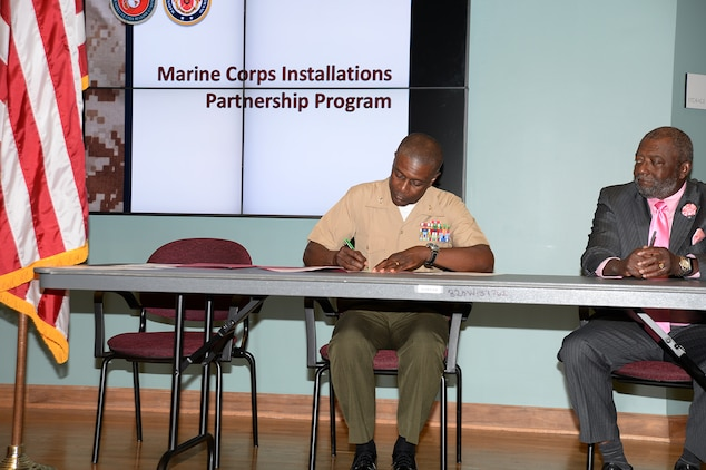 Col. James C. Carroll III, commanding officer, Marine Corps Logistics Base Albany, left, signs an educational partnership agreement with Dr. Anthony Parker, president, Albany Technical College at ATC, Albany, Ga., recently.