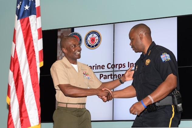 Col. James C. Carroll III, commanding officer, Marine Corps Logistics Base Albany, left, congratulates Michael Persley, chief of police, City of Albany, on their new S.W.A.T. partnership agreement at Albany Technical College, Albany, Ga., recently.