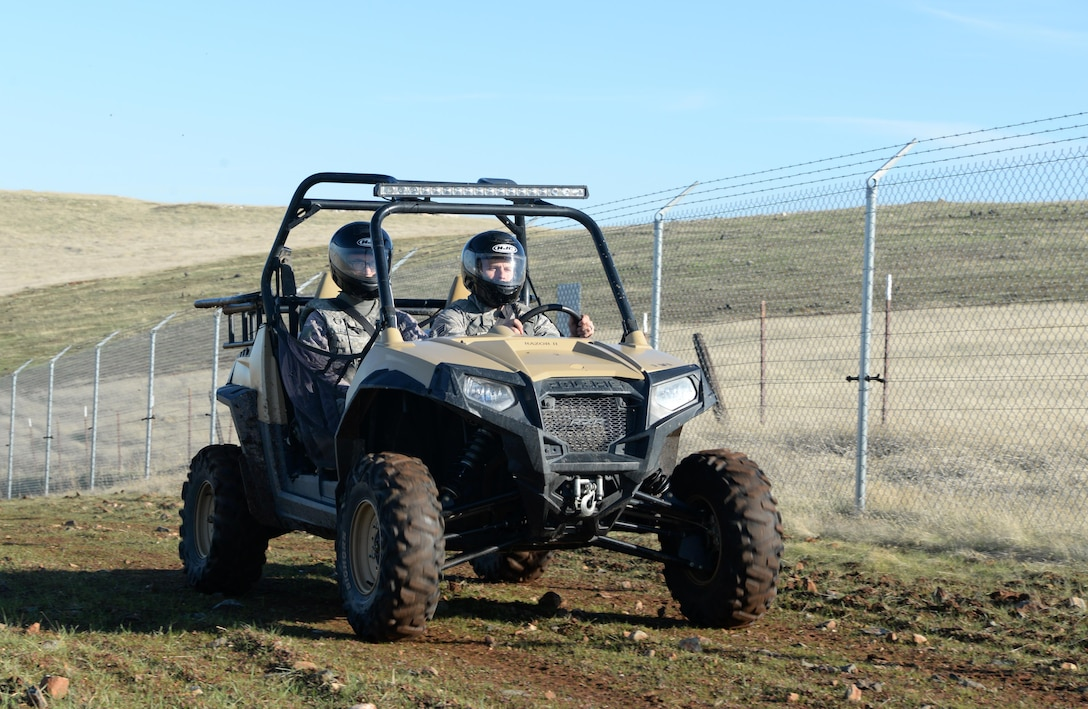Senior Airman David Gill, 9th Security Forces Squadron base defense operation controller, and Airman 1st Class Luis Valentin, 9th SFS installation entry controller, drive an all-terrain vehicle alongside a fence line Nov. 4, 2016, at Beale Air Force Base, California. The perimeter of Beale is 26 miles and is broken up into six sectors. (U.S. Air Force photo/Airman Tristan D. Viglianco)