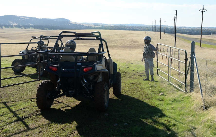 Airman 1st Class Luis Valentin, 9th Security Forces Squadron installation entry controller, opens a gate for the all-terrain vehicles to drive through Nov. 4, 2016, at Beale Air Force Base, California. On coyote patrols security forces' personnel inspect the fence line and gates on the outskirts of the installation. (U.S. Air Force photo/Airman Tristan D. Viglianco)