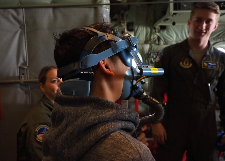 A member of the Ames High School orchestra tries on an oxygen mask aboard a C-130 as Staff Sgt. Hannah Currie and Senior Airman James Dennis, 934th Aeromedical Evacuation Squadron, look on.