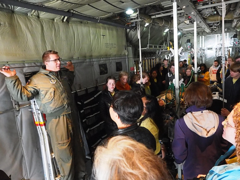 Staff St. James Goetze, 96th Airlift Squadron loadmaster, explains some of the capabilities of the C-130 to members of the Ames High School Orchestra.