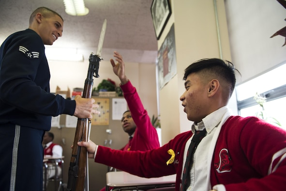 Senior Airman Angelo Hightower, U.S. Air Force Honor Guard Drill Team member, lets a La Salle Academy student hold his drill rifle during a school visit in New York, Nov. 10, 2016. The rifles are approximately 12 pounds and have dull bayonets attached at the end. (U.S. Air Force photo by Senior Airman Philip Bryant)
