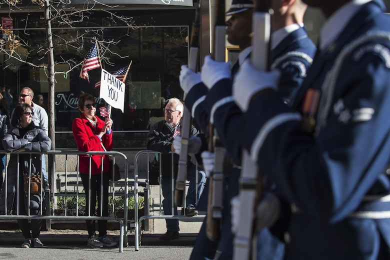 A parade viewer holds a sign of thanks while the U.S. Air Force Honor Guard march in the 2016 America's Parade on Veterans Day down Fifth Avenue in Manhattan New York, Nov. 11, 2016. The parade had thousands of viewers lining Fifth Avenue with American flags and signs showing their support of past and present veterans. (U.S. Air Force photo by Senior Airman Philip Bryant)