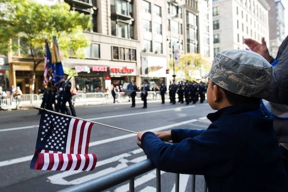A young parade viewer watches the U.S. Air Force Honor Guard march in the 2016 America's Parade on Veterans Day down Fifth Avenue in Manhattan New York, Nov. 11, 2016. The parade had thousands of viewers lining Fifth Avenue with American flags and signs showing their support of past and present veterans. (U.S. Air Force photo by Senior Airman Philip Bryant)