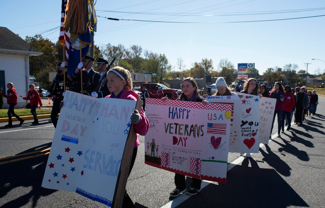 Children with signs and flags walked alongside the U.S. Air Force Honor Guard as they march in the 4th Annual Veterans Day Parade in Laurel, Del., Nov. 12, 2016. Laurel is a small city with a population of approximately 3,700, most taking part in the parade. (U.S. Air Force photo by Senior Airman Philip Bryant)