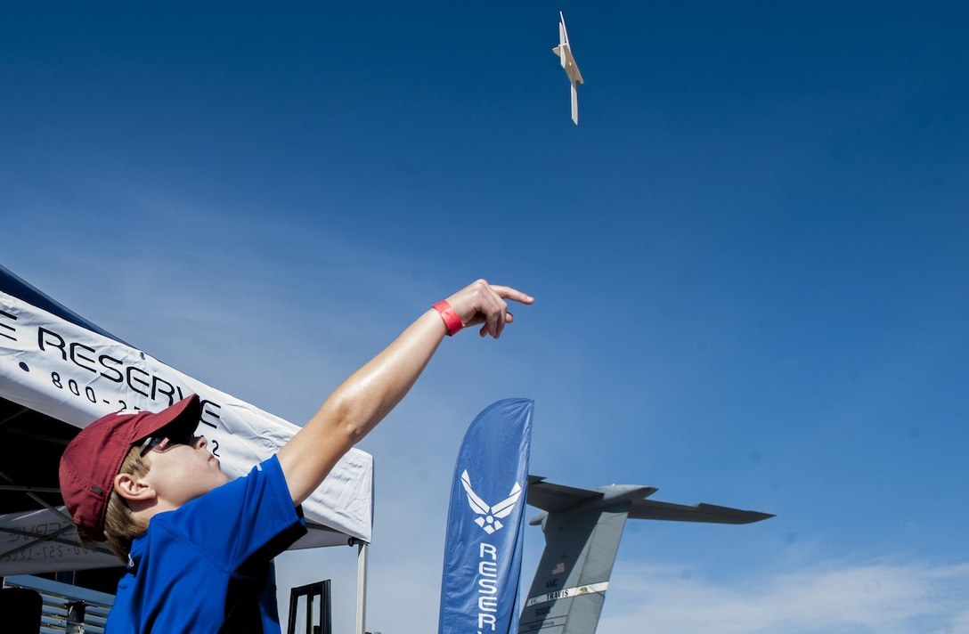 A boy throws a model airplane during the Aviation Nation air show on Nellis Air Force Base, Nev., Nov. 12, 2016. Aviation Nation provided the community the opportunity to interact with Airmen. (U.S. Air Force photo by Airman 1st Class Kevin Tanenbaum/Released)