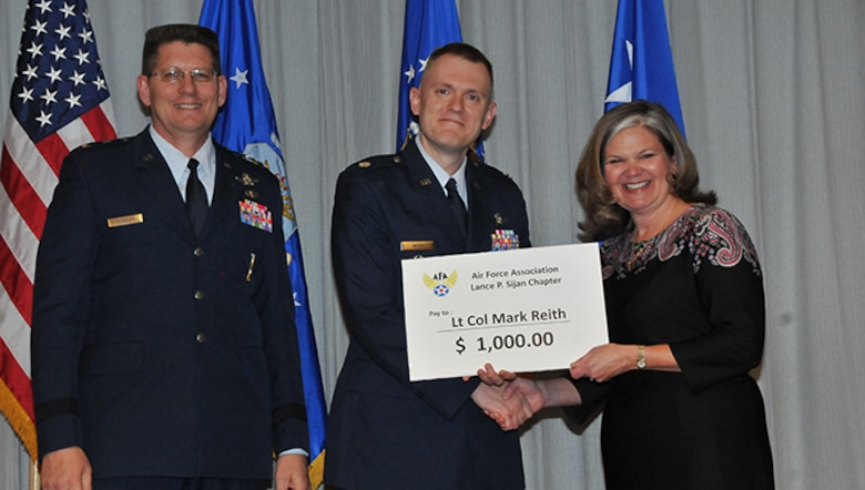 Several Airmen received prizes and recognition at an award ceremony on Nov. 15, 2016 at Peterson AFB for their winning essays in the 2016 Gen. Bernard A. Schriever Memorial Essay Contest.  Pictured from left to right are AFSPC vice commander Maj. Gen. David Thompson, Open Division winning essay author Lt. Col. Mark Reith and incoming AFA Lance P. Sijan Chapter president Kristen Christy
