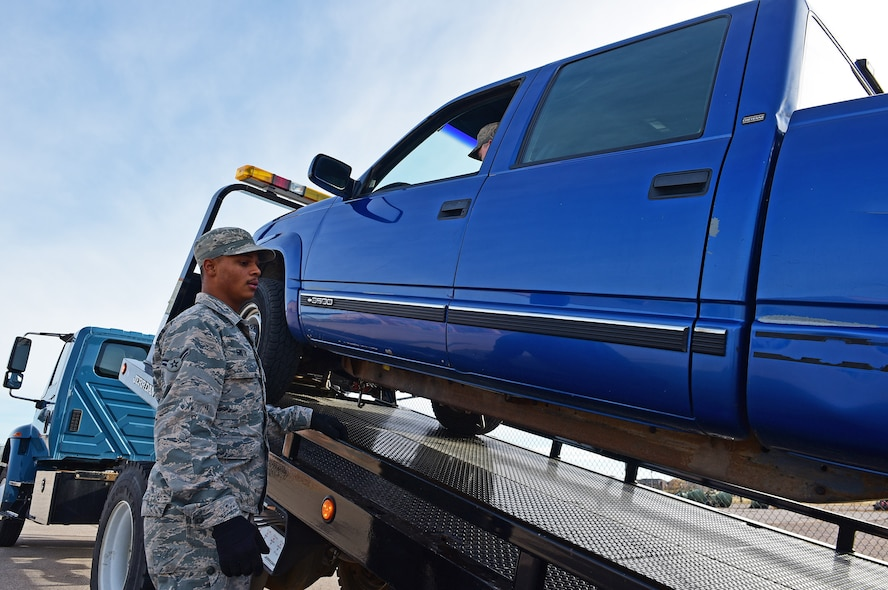 Airman 1st Class Jordan Smith, a vehicle operations apprentice assigned to the 28th Logistics Readiness Squadron, uses a winch to prepare a truck to be towed for repairs at Ellsworth Air Force Base, S.D., Nov. 8, 2016. Vehicle operators are responsible for ensuring the readiness of government vehicles on Ellsworth. (U.S. Air Force photo by Airman 1st Class James L. Miller)