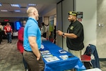 A representative from the Disabled American Veterans talks to a DSCC associate about what the charity offers during a Veterans Benefits fair Nov. 9 inside the DLA land and Maritime Operations Center. The fair was held in conjunction with the DSCC Veterans Day Program.