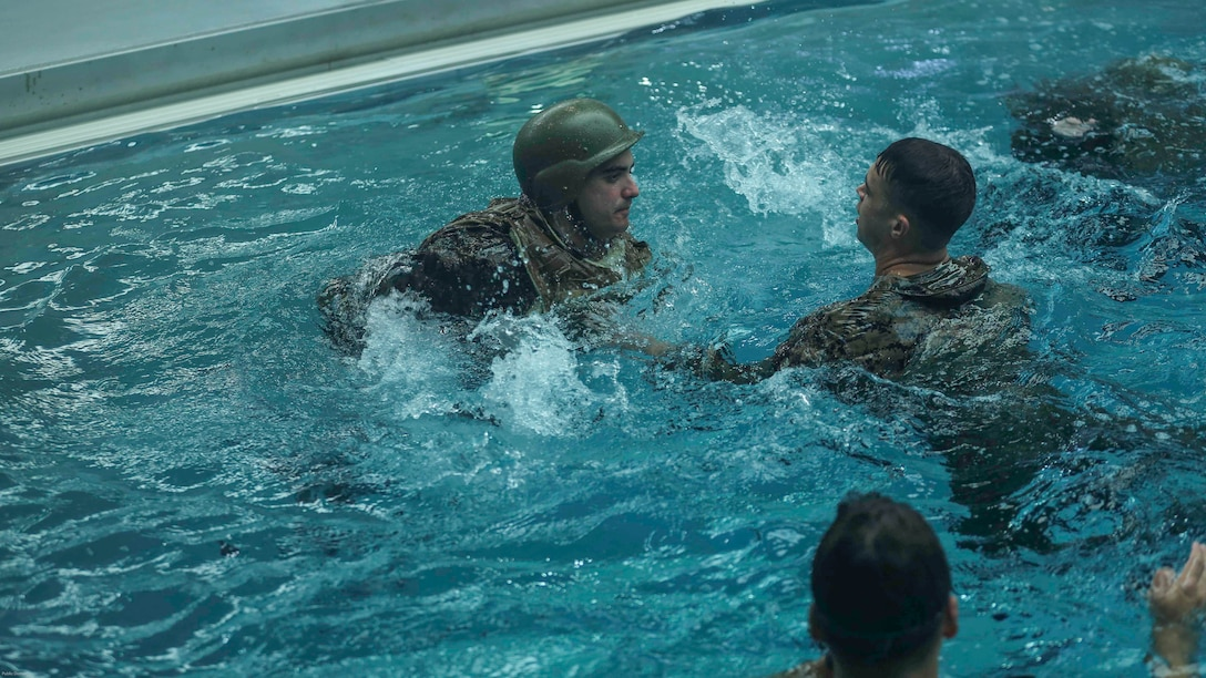 """Marines practice rescuing notional victims with full combat gear during an advanced water survival qualification course at Camp Lejeune, N.C., Nov. 8, 2016. """"The survival strokes are for efficiency, not speed,"""" said Sgt. Sasha McFadden, a Marine Combat Instructor of Water Survival Instructor with 2nd Radio Battalion."""