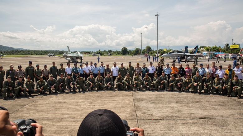 U.S. Marines with Marine All-Weather Fighter Attack Squadron 225, U.S. Air Force Maj. Gen. Mike Compton, Air National Guard assistant to the commander, Pacific Air Forces, Indonesian Air Force service members and Indonesian Air Vice Marshal Barhim, Air Force Chief Operations Assistant, pose for a photo during a closing ceremony for exercise Cope West 17 at Sam Ratulangi International Airport, Indonesia, Nov. 11, 2016. This fighter-focused, bilateral exercise between the U.S. Marine Corps and Indonesian Air Force is designed to enhance the readiness of combined interoperability between the two nations.