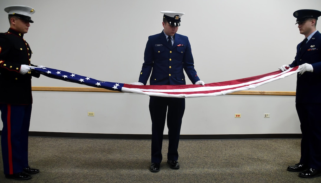 Members of a veteran's color guard team perform a flag-folding ceremony while describing the significance of the American Flag, Nov. 10, 2016, at Buckley Air Force Base, Colo.  The folding of the flag at ceremonies is a traditions that has been practiced for multiple generations.(U.S. Air Force photo by Airman Holden S. Faul/ Released)