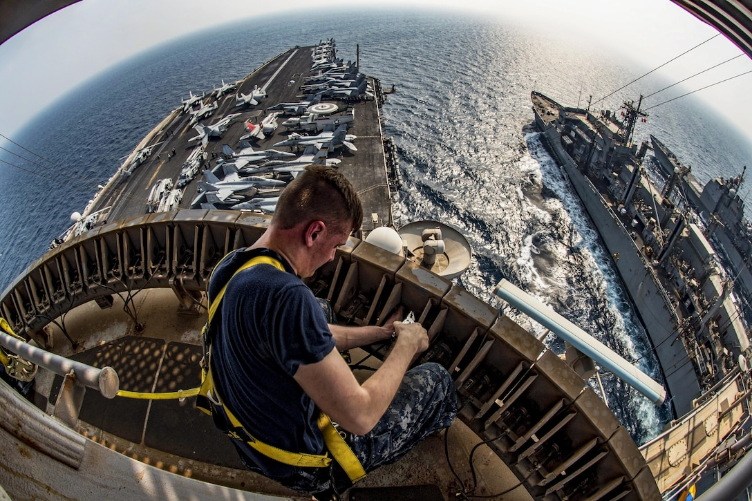 Navy Petty Officer 3rd Class Brian Evans maintains an antenna system while working aloft during a replenishment involving the USS Dwight D. Eisenhower, the USS Monterey and the USNS Arctic in the Persian Gulf, Sept. 2, 2016. The Eisenhower is supporting Operation Inherent Resolve in the U.S. 5th Fleet area of operations. Navy photo by Petty Officer 3rd Nathan T. Beard