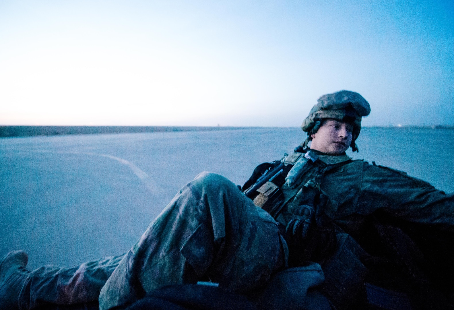 Senior Airman Jacob Brooks, 821st Contingency Response Group aircraft maintainer, catches a ride in the back of a utility vehicle out to the airstrip at Qayyarah West Airfield, Iraq, in support of Combined Joint Task Force - Operation Inherent Resolve, Nov. 14, 2016. The airfield at Qayyarah West was recaptured from Da'esh by Iraqi forces in July 2016, and has been refurbished by Coalition engineers to allow the re-commencement of air operations. Qayyarah Airfield is now a vital logistical hub, opening an air corridor in support of the battle to liberate Mosul as well as operations throughout northern Iraq. (U.S. Air Force photo by Senior Airman Jordan Castelan)