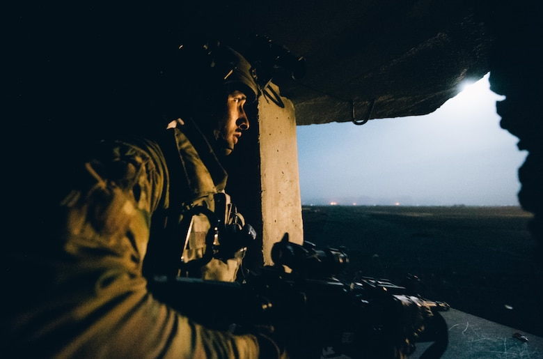 Senior Airman Ralph Hoeflich, 821st Contingency Response Group close precision engagement airman, scans a field illuminated by a flare from inside a defensive fighting position at Qayyarah West Airfield, Iraq, in support of Combined Joint Task Force - Operation Inherent Resolve, Nov. 14, 2016. The 821st CRG is highly-specialized in training and rapidly deploying personnel to quickly open airfields and establish, expand, sustain and coordinate air operations in austere, bare-base conditions. (U.S. Air Force photo by Senior Airman Jordan Castelan)
