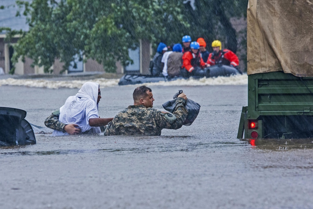 Two guardsmen carry a resident through flood waters to a vehicle.