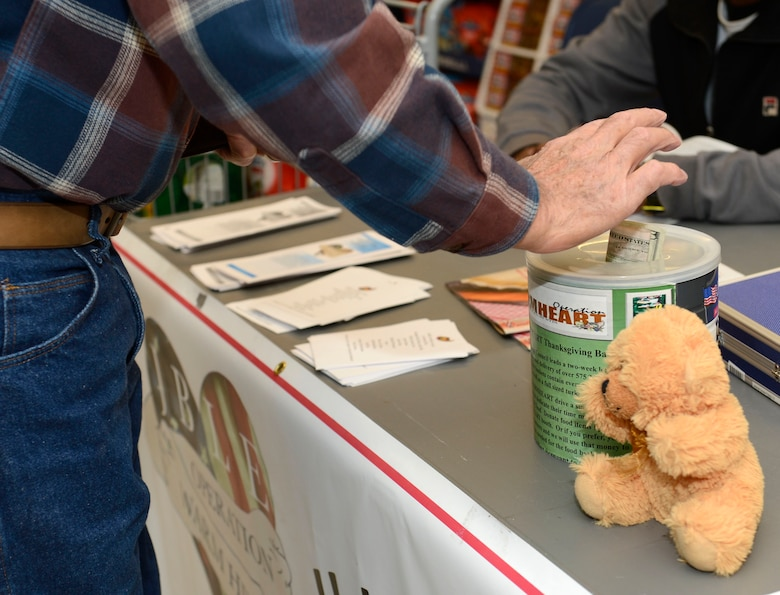A commissary customer donates money to Operation Warmheart at Joint Base Langley-Eustis, Va., Nov. 15, 2016. Operation Warmheart is a nonprofit organization established by the First Sergeants Council to assist Joint Base Langley-Eustis service members and their families in need, through charitable funds raised throughout the year. (U.S. Air Force photo by Airman 1st Class Kaylee Dubois)