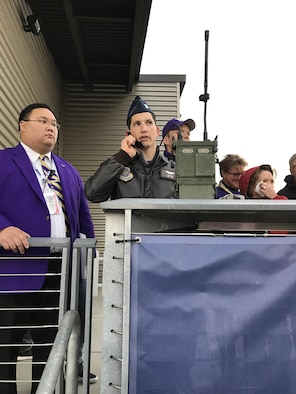 Capt. Anthony Bianchi, 62nd Operations Support Squadron executive officer, and Josh T. Chan, Husky Athletic Bands and Spirits Squads program coordinator, work to get the C-17 Globemaster III flyover timed perfectly for the University of Washington pre-game Veterans Day salute Nov. 12. (U.S. Air Force photo by Jason Waggoner)