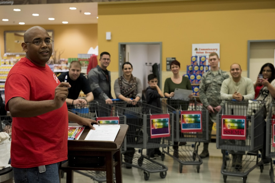 U.S. Air Force Staff Sgt. Willie Moore, left, 52nd Maintenance Squadron propulsion test cell supervisor, explains rules to contestants during the annual Spangdahlem Spouses and Enlisted Members Club Commissary Sweep at Spangdahlem Air Base, Germany, Nov. 15, 2016. During the event, Airmen and families guessed food item prices, answered riddles and shopped against the clock without exceeding their given allowance in order to win various amounts of commissary gift cards. (U.S. Air Force photo by Airman 1st Class Preston Cherry)