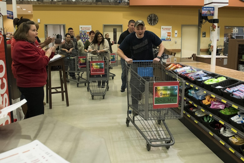 Contestants race toward the aisles during the Spangdahlem Spouses and Enlisted Members Club Commissary Sweep at Spangdahlem Air Base, Germany, Nov. 15, 2016. During the event, Airmen and families guessed food item prices, answered riddles and shopped against the clock without exceeding their given allowance in order to win commissary gift cards. (U.S. Air Force photo by Airman 1st Class Preston Cherry)
