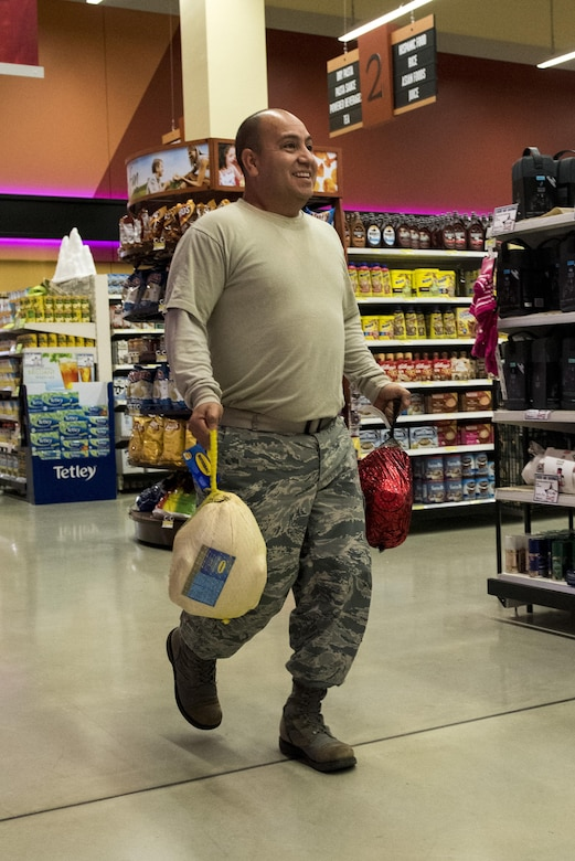U.S. Air Force Staff Sgt. David Gomez, 52nd Force Support Squadron training manager, races down an aisle during the Spangdahlem Spouses and Enlisted Members Club Commissary Sweep at Spangdahlem Air Base, Germany, Nov. 15, 2016. The event gave participants the opportunity to receive free groceries and Commissary gift cards ranging from $50 to $200. (U.S. Air Force photo by Airman 1st Class Preston Cherry)