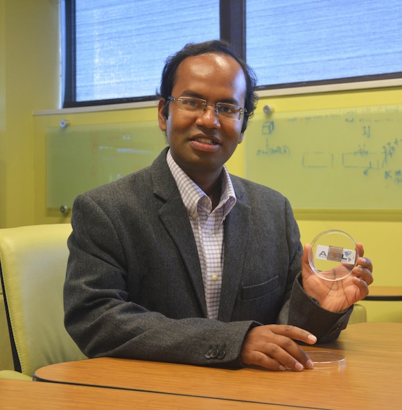 Dr. Santanu Bag holds a thin-film perovskite solar cell developed by the AFRL research team.  These transparent and more-efficient solar cells could play an integral role next-generation Air Force power applications. (U.S. Air Force Photo/David Dixon)