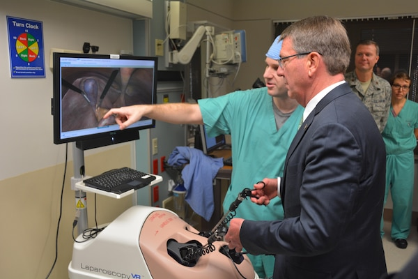 Secretary of Defense Ash Carter steadies his hand using the Laparoscopy simulator under the trained eyes of U.S. Army Maj. John Ritchie during his November 16 visit to Brooke Army Medical Center, Fort Sam Houston, Texas. BAMC is the Army's largest and busiest medical center. Secretary Carter personally thanked wounded and ill warriors, their families and BAMC staff for their service and sacrifice. Secretary Carter toured labs and simulation centers pioneering new advances in diagnostic imaging and new medical training aids. His visit at BAMC was part of a tour of Joint Base San Antonio, with stops at JBSA-Lackland and JBSA-Randolph. (U.S. Army photo by Robert Shields/Released)