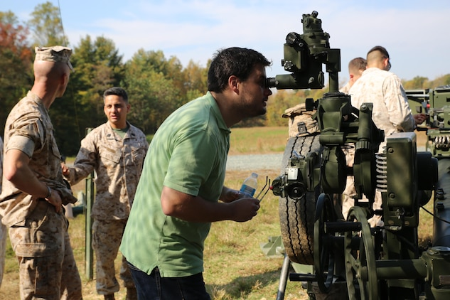 Caleb Hughes, the large-caliber ammunition engineer at MCSC's Ammunition Program Management Office, looks through a sight used to align the M777 howitzer to a target during a field artillery demonstration at Marine Corps Training Command aboard Marine Corps Base Quantico last month. During the demonstration MCSC employees gained first-hand experience of field artillery Marines in action to inform their work behind the scenes at MCSC. (U.S. Marine Corps photo by Mathuel Browne)