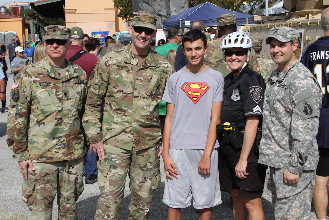 SAN ANTONIO - Local police officer Donna Marti and son Zane pose with soldiers in front of the1st Cavalry static display at the 'Army vs Irish' game held at the Alamodome November 12, 2016. As part of the Alamodome static display section, the 1st Calvary provided a M2 Bradley Fighting Vehicle for the public to experience. (Photo by Sgt. Zechariah Gerhard, 345th Public Affairs Detachment)