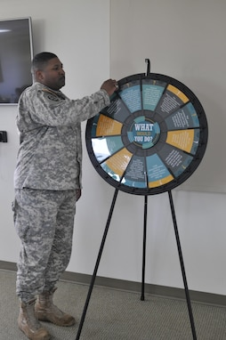 Sgt. 1st Class James Glass, senior supply non-commissioned officer, 351st Civil Affairs Command, spins the 'what would you do' wheel to take a chance at solving a Sexual Harassment/Assault Response scenario, Nov. 9, Camp Parks, Dublin, Calif. The wheel was repeatedly used as a creative teaching method to prepare for real occurrences after graduating as Sexual Assault Response Coordinators. (U.S. Army Reserve photo by Sgt. 1st Class LaTonya Kelly)