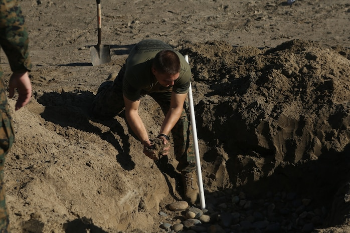 U.S. Navy Petty Officer 2nd Class Michael Mathews helps to set up a grey water sanitation soakage pit during Preventative Medicine Exercise 2016 at Camp Pendleton, Calif., Nov. 10, 2016. The pit is 5 feet long, 5 feet wide, and 5 feet deep filled with small rocks and pipes to safely transfer waste to the ground. Grey water is any substance that could potentially be harmful to the environment and special precautions are made to keep the exercise's area safe. Matthews is a preventive medical technician with 1st Medical Battalion, 1st Marine Logistics Group. (U.S. Marine Corps photo by Lance Cpl. Joseph Sorci)