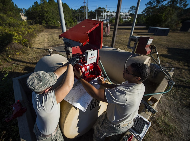 Senior Airmen Dacota Napolitano, left, and Chris Coney, water and fuels system specialists with the 1st Special Operations Civil Engineer Squadron, remove a fuel pump from a fuel tank at Hurlburt Field, Fla., Nov. 17, 2016. The fuel tanks are used to hold fuel for lawn maintenance equipment that maintain Hurlburt's Gator Lakes Golf Course. (U.S. Air Force photo by Airman 1st Class Joseph Pick)