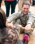 TOGIAK, Alaska -- Staff Sgt. Katelyn Martell, with the Air Force Reserve's 55th Aerial Port Squadron, competes in an Eskimo stick contest with a schoolgirl here Nov. 15, 2016. Martell was one of a handful of reservists who traveled here from Travis Air Force Base, Calif., to assist the Alaska National Guard with Operation Santa Claus 2016. Now in its 60th year, Operation Santa Claus is an Alaska National Guard-led program that delivers toys, school supplies and other gifts to children in Alaska's remote villages. National Guard photo by Maj. John Callahan.