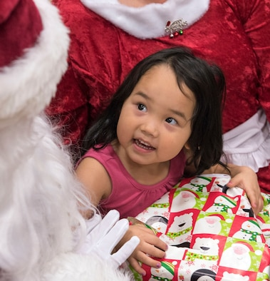 TOGIAK, Alaska -- Cassadee Mooore, 3, beams up at Santa in the school gymnasium here Nov. 15, 2016. The Clauses were here as part of Operation Santa Claus, an Alaska National Guard-led program that delivers toys, school supplies and other gifts to children in Alaska's remote villages. Air National Guard photo by Maj. John Callahan.