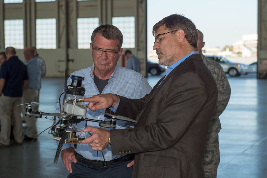 Defense Secretary Ash Carter observes static displays of advanced weapons and unmanned aerial systems.