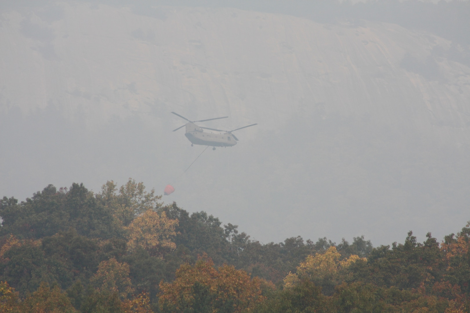 A South Carolina Army National Guard CH-47 Chinook from Det. 1, Bravo Company, 2-238th General Support Aviation Battalion with Soldiers from Donaldson Field in Greenville, South Carolina, responded to a request for help from the South Carolina Forestry Commission to contain fires burning near the top of Pinnacle Mountain in in Pickens County, South Carolina, Nov. 15, 2016.  The aircraft is equipped with a Bambi Bucket, which can be filled with any available water to be transported and dumped on the fire.