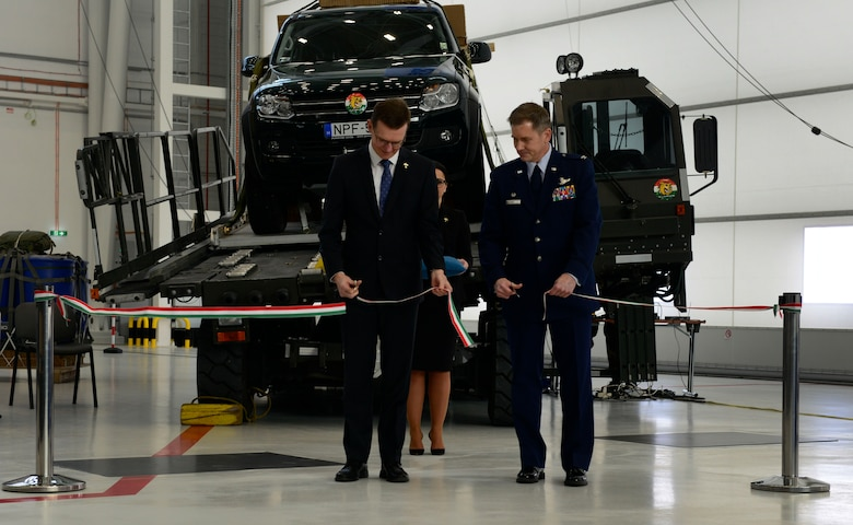 Wiek Noldus, NATO Support Agency Airlift Management program manager, and U.S. Air Force Col. Trevor Nitz, Heavy Airlift Wing commander, cut a ribbon signifying the grand opening of a new C-17 Globemaster III hangar complex at Pàpa Air Base, Hungary on Nov. 17, 2016. The hangar complex will allow the HAW to perform maintenance on the Strategic Airlift Capability program's three C-17s. (U.S. Air Force photo by Staff Sgt. Krystal Ardrey)