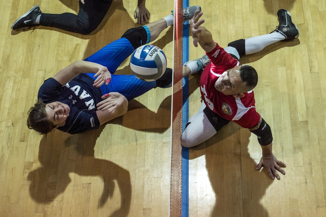 Navy Lt. Joan Hill, left, and Marine Gunnery Sgt. Andrew Cordova battle at the net during the 2016 Warrior Care Month Joint Service Sitting Volleyball Tournament.