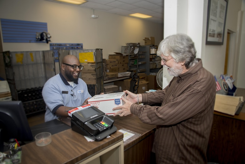 Kenneth Collins (left), United States Postal Services sales and services associate, receives a package from Joe Beach, 502nd Air Base Wing Public Affairs graphic artist, Nov. 15 at the Joint Base San Antonio-Randolph Post Office. The holiday rush at U.S. Postal Service locations is near at hand, so it's advisable for the families of active-duty members who are serving abroad to mail cards, letters and packages to their loved ones as soon as possible.