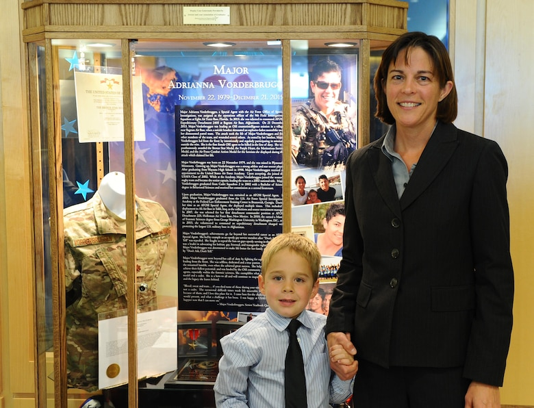 Heather Lamb stands in front of a memorial display honoring her wife, Maj. Adrianna Vorderbruggen, with the couples son, Jacob, Nov. 12, 2016, at the Air Force Academy. Vorderbruggen, a 2002 Academy graduate, was a U.S. Air Force Office of Special Investigations agent who died in Afghanistan last year. (U.S. Air Force photo/Tech. Sgt. Mike Slater)