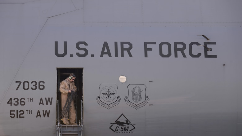 Staff Sgt. Brian Covert, a 9th Airlift Squadron flight engineer, gathers communication chords during post-flight duties at Aviano Air Base, Italy, Nov. 8, 2016. The C-5M Super Galaxy arrived at Aviano AB for cargo loading on its way to Iraq. Two teams spent approximately two hours loading and securing the cargo before the C-5 was prepared for takeoff. (U.S. Air Force photo/Senior Airman Cary Smith)