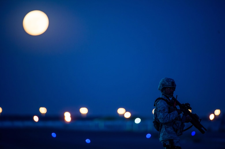 A member of the 380th Air Expeditionary Wing security forces stands on a flightline near a guard tower at an undisclosed location in Southwest Asia Nov. 14, 2016. Behind the Airman a rare supermoon rises in the sky. The moon has not been closer to the Earth since Jan. 26, 1948. (U.S. Air Force photo/Senior Airman Tyler Woodward)