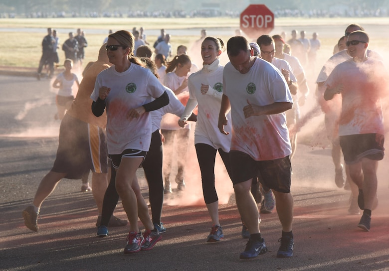 Col. Michele Edmondson, 81st Training Wing commander, and Chief Master Sgt. Anthony Fisher, 81st Training Group superintendent, participate in a Wing color run at the Marina Park Nov. 17, 2016, on Keesler Air Force Base, Miss. The run was one of several events held throughout Dragon Week, which focuses on resiliency and teambuilding initiatives across the base. (U.S. Air Force photo by Kemberly Groue/Released)