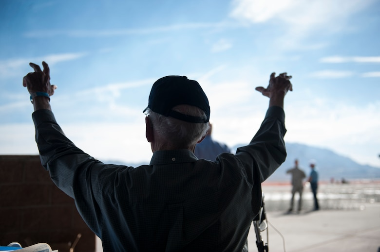 Lenoard Nielson, U.S. Navy Pearl Harbor survivor raises his hands with excitement during the Aviation Nation air show at Nellis Air Force Base, Nev., Nov. 12. This year, Aviation Nation celebrated 75 years of Air Power through the Air Force's accomplishments  in air, space and cyberspace. During the two-day event, there were more than 50 aircraft on display along with an array of vendors and aerial demonstrations for viewers. (U.S. Air Force photo by Senior Airman Rachel Loftis/released)