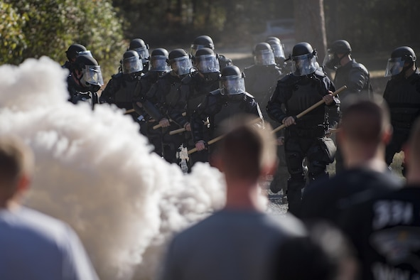 Members of Georgia State Patrol's Mobile Field Force march toward a group of simulated rioters while a smoke grenade burns, Nov. 16, 2016, at Moody Air Force Base, Ga. Between the two days of training, approximately 45 GSP officers participated in the training. (U.S. Air Force photo by Airman 1st Class Daniel Snider)