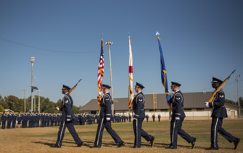 An Honor Guard team carries the colors by a line of Airmen waiting for their moment to enter the Community College of the Air Force graduation ceremony at Eglin Air Force Base, Fla., Nov. 16.  More than 300 Airmen from Eglin and Duke Field were honored at this year's event. (U.S. Air Force photo/Samuel King Jr.)