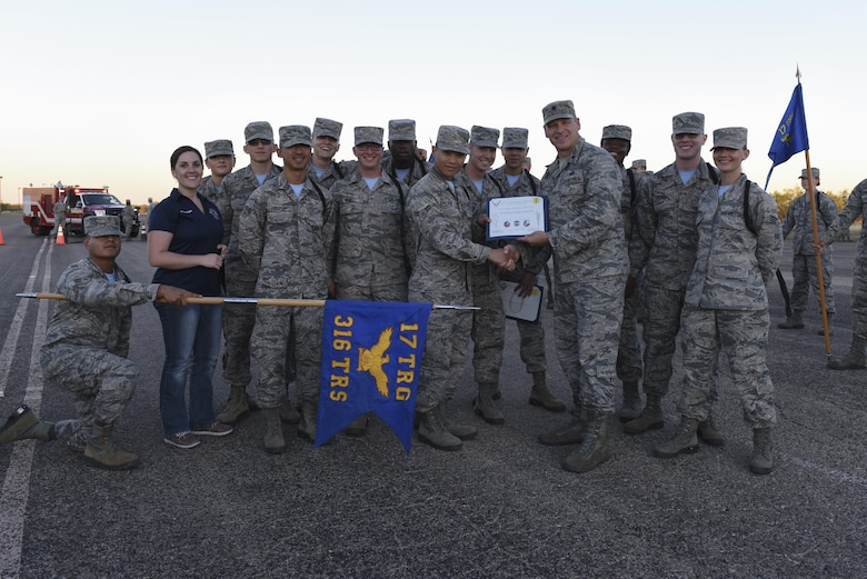 316th Training Squadron Airmen stand with their award as best drill team at the flight line on Goodfellow Air Force Base, Texas, Nov. 16, 2016. The 316th TRS drill team beat the 312th Training Squadron and 315th Training Squadron. (U.S. Air Force photo by Airman 1st Class Chase Sousa/Released)